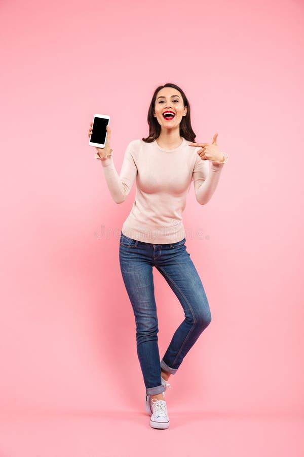 Foto completa do comprimento do demonstrat vestindo adorável das calças de brim da mulher 20s fotografia de stock