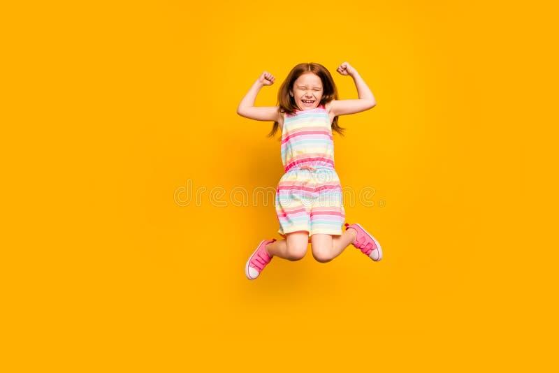 Foto completa do corpo do salto de encantamento da criança isolada sobre o fundo amarelo foto de stock royalty free