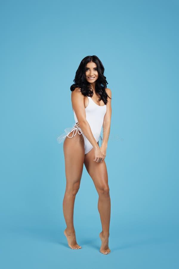 Foto completa dos lenhts de uma jovem mulher entusiasmado vestida no roupa de banho branco que levanta no fundo azul fotos de stock