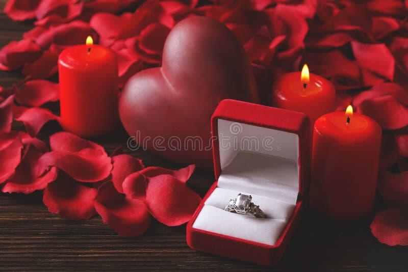 Foto conceptual do casamento ou do anel de noivado com velas na forma do coração St Dia do ` s do Valentim imagens de stock