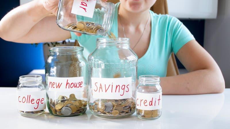 Foto conceptual do close up de economias de controlo do orçamento e do dinheiro de família da jovem mulher fotos de stock