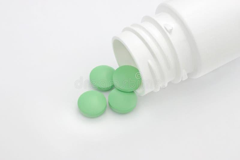 foto conceptual médica Píldoras farmacéuticas redondas verdes que se derraman fuera de una botella de píldora blanca foto de archivo libre de regalías