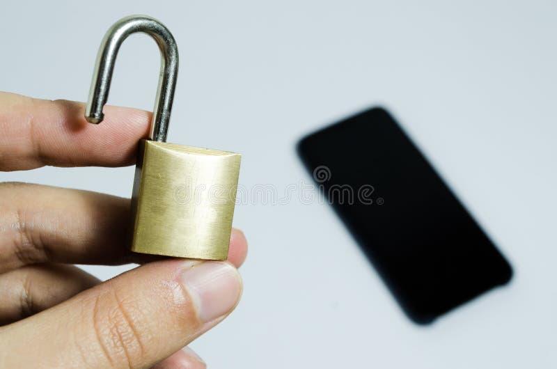Foto concettuale di sicurezza sui telefoni cellulari Mano che tiene un lucchetto aperto e un telefono cellulare nei precedenti fotografia stock