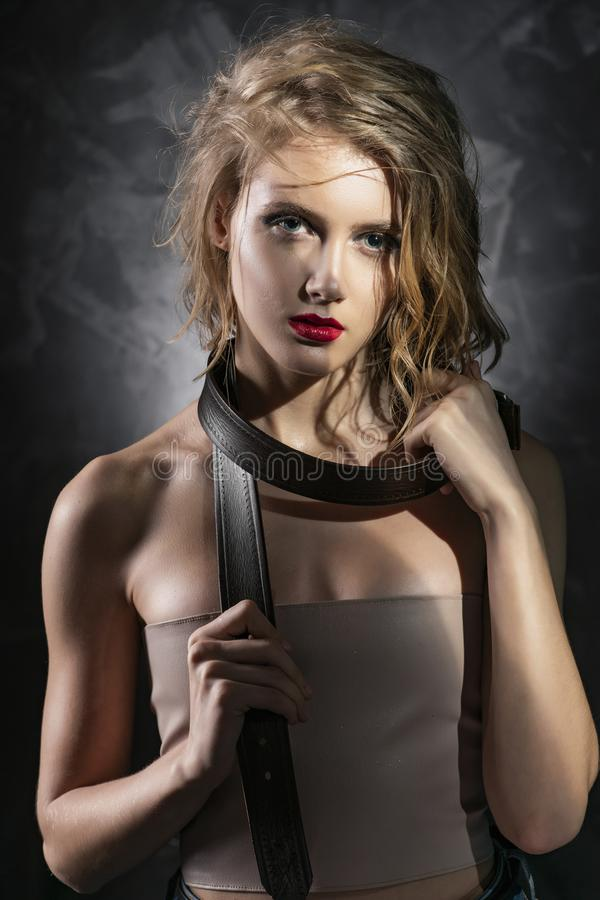 Foto concettuale di una ragazza con capelli bagnati scompigliati, le spalle nude, il trucco aggressivo e una cinghia di cuoio deg immagine stock libera da diritti