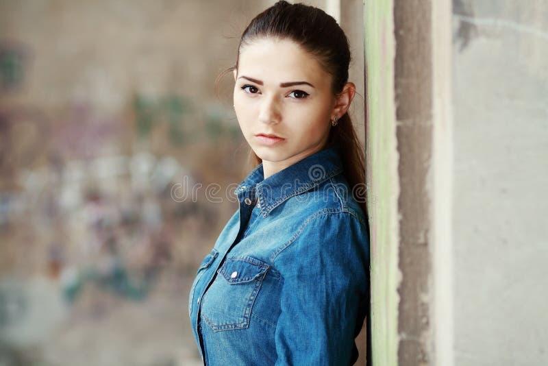 Foto conservada em estoque de uma menina de encontro à parede azul imagens de stock royalty free