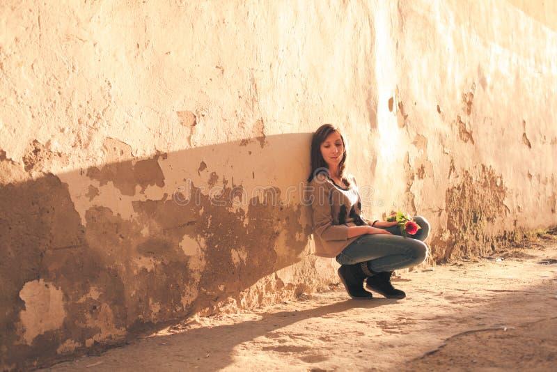 Foto conservada em estoque de uma menina de encontro à parede azul imagem de stock