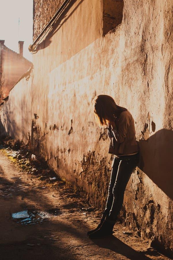 Foto conservada em estoque de uma menina de encontro à parede azul foto de stock royalty free