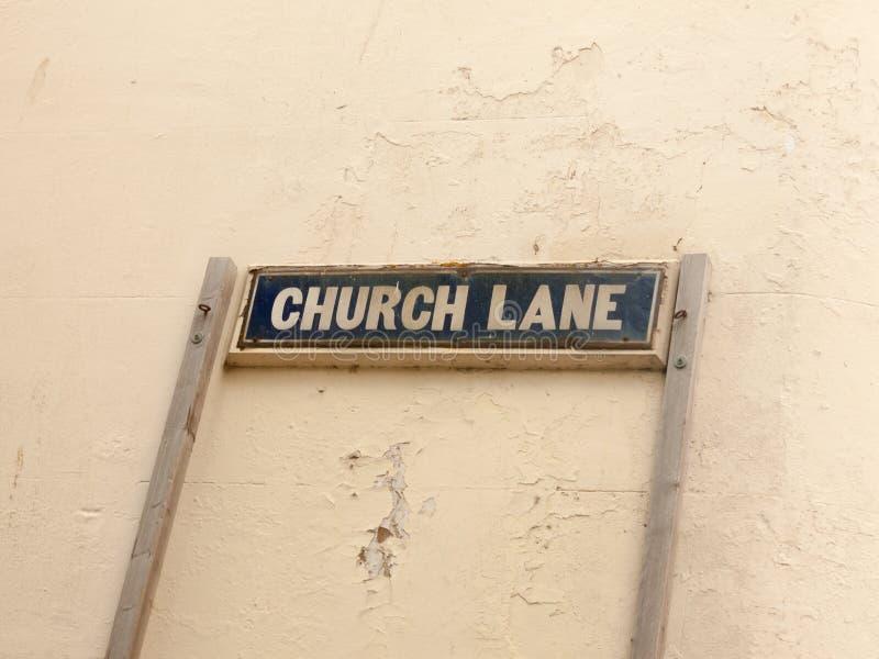 Foto conservada em estoque - pista da igreja do sinal de rua contra a parede branca fotografia de stock royalty free