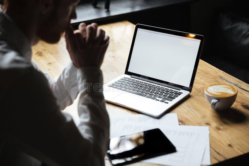 Foto cosechada del hombre de negocios que se sienta en la tabla de madera, foco en l fotografía de archivo