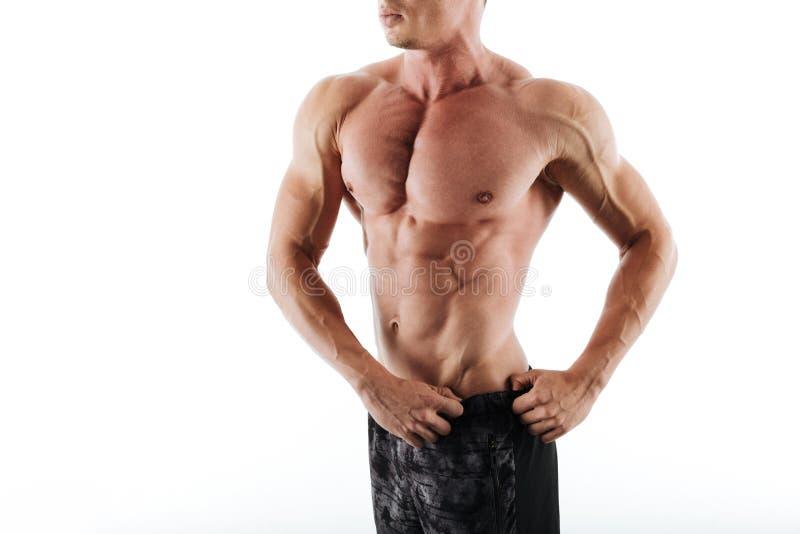 Foto cosechada del hombre muscular cauccasian joven en pantalones cortos negros foto de archivo