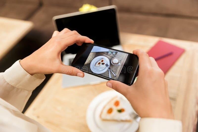 Foto cosechada del sombrero que lleva de la mujer caucásica que fotografía la comida en el teléfono celular imagen de archivo