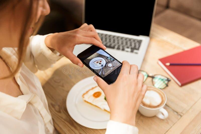 Foto cosechada del sombrero que lleva de la mujer joven que fotografía la comida en el teléfono celular fotografía de archivo libre de regalías