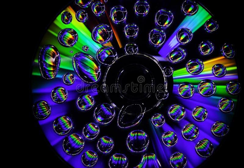 Foto creativa con un CD con las grandes luces y waterdrops en la superficie en fondo negro foto de archivo