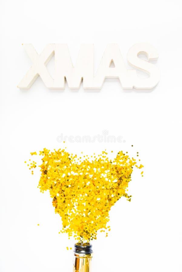 Foto creativa di bottiglia di champagne con coriandoli su fondo bianco con una decorazione gigante di xmas in alto, Piatto di nat fotografie stock