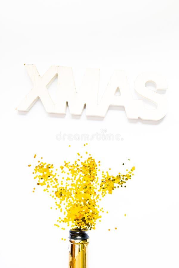 Foto creativa di bottiglia di champagne con coriandoli su fondo bianco con una decorazione gigante di xmas in alto, Piatto di nat fotografia stock libera da diritti