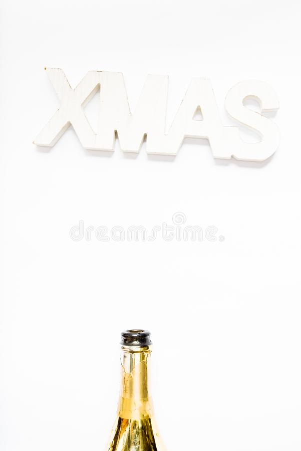 Foto creativa di bottiglia di champagne con coriandoli su fondo bianco con una decorazione gigante di xmas in alto, Piatto di nat immagini stock libere da diritti