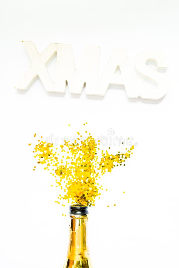 Foto creativa di bottiglia di champagne con coriandoli su fondo bianco con una decorazione gigante di xmas in alto, Piatto di nat immagine stock