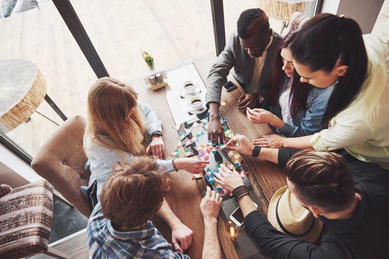 Foto criativa da vista superior dos amigos que sentam-se na tabela de madeira Amigos que têm o divertimento ao jogar o jogo de me imagem de stock
