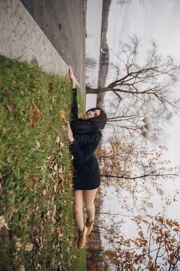 Foto criativa de uma menina moreno no parque do outono Mulher que pendura da borda, encontrando-se na grama verde Olhe o mundo do imagens de stock