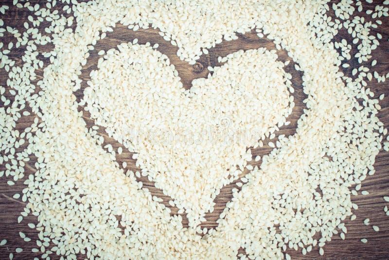 Foto d'annata, cuore dei semi di sesamo a bordo, concetto di nutrizione e sumbol sani di amore fotografia stock libera da diritti