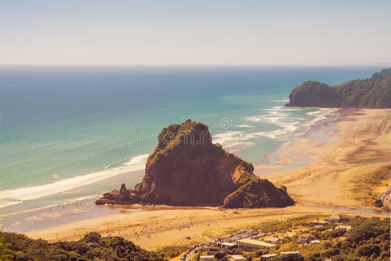 Foto d'annata di Lion Rock nel centro della spiaggia di Piha un bello giorno di estate Auckland, Nuova Zelanda immagini stock libere da diritti