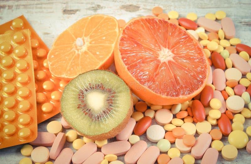 Foto d'annata, frutti e pillole naturali, scelta fra nutrizione sana e supplementi immagini stock