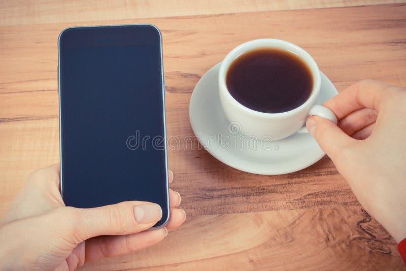 Foto d'annata, mano dello schermo in bianco commovente della donna del telefono cellulare, tazza di caffè fotografia stock