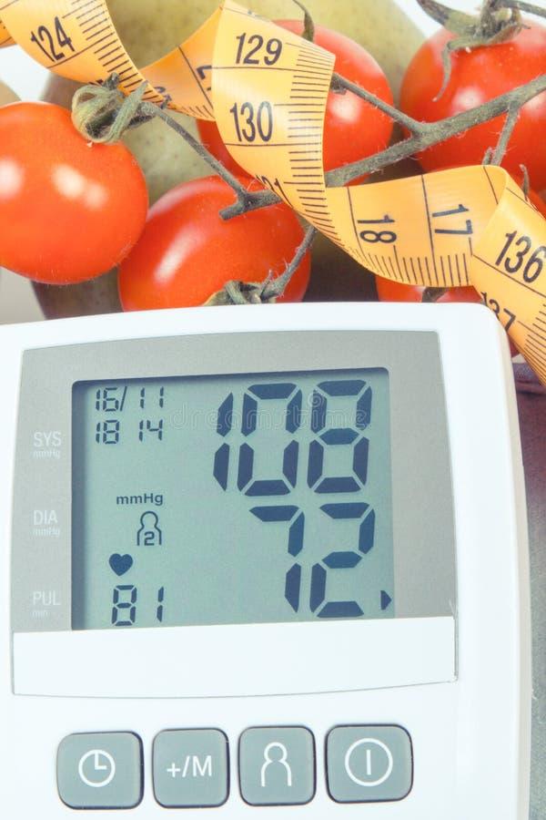 Foto d'annata, monitor di pressione sanguigna con il risultato della misura, frutti con le verdure e centimetro, stile di vita sa immagini stock libere da diritti