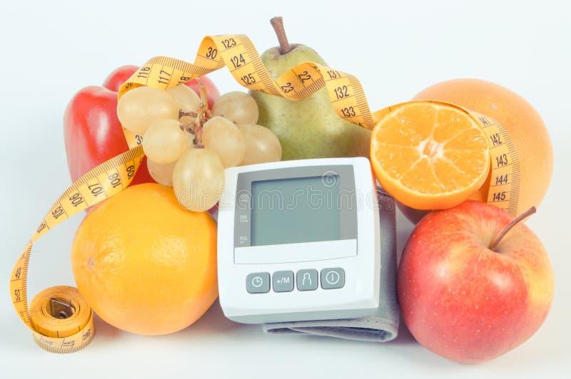 Foto d'annata, monitor di pressione sanguigna, frutta fresca con le verdure e centimetro, stile di vita sano fotografia stock