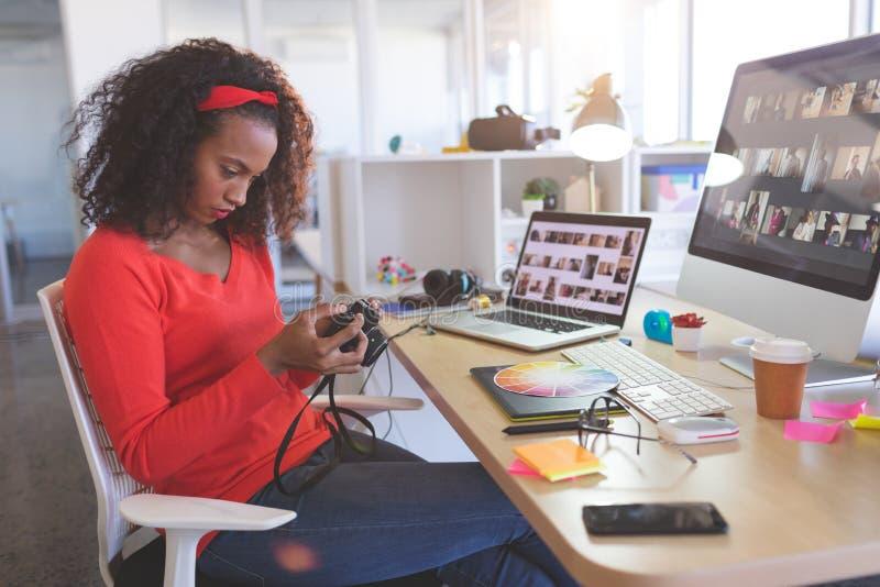 Foto d'esame del grafico femminile in macchina fotografica digitale allo scrittorio immagini stock libere da diritti