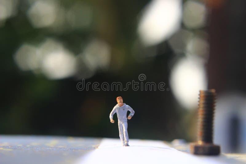 Foto d'illustrazione: Cheap and Easy Sport al mattino, Uomo Giocattolo di una Mini Figura ad Asphalt Road fotografia stock libera da diritti