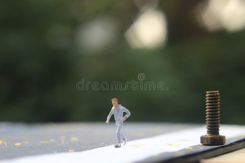 Foto d'illustrazione: Cheap and Easy Sport al mattino, Uomo Giocattolo di una Mini Figura ad Asphalt Road fotografia stock