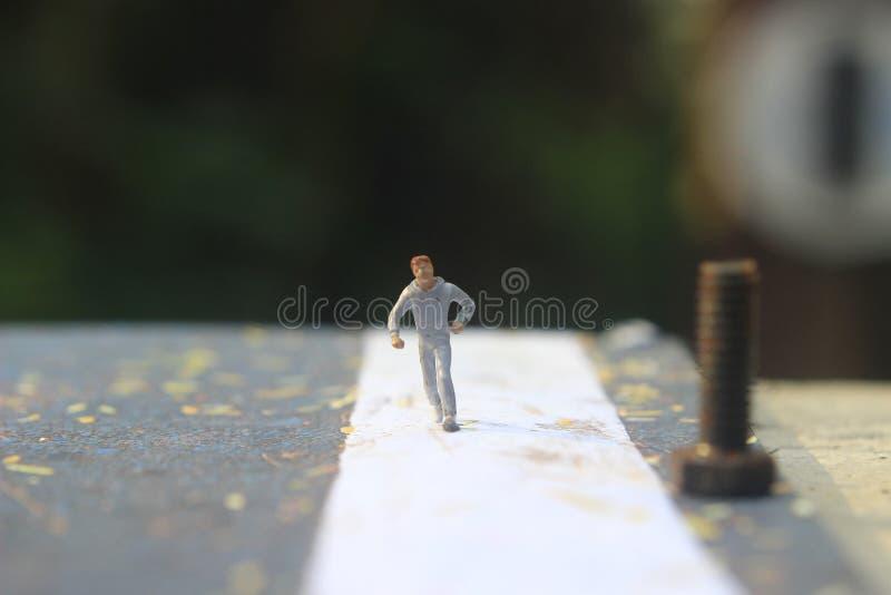 Foto d'illustrazione: Cheap and Easy Sport al mattino, Uomo Giocattolo di una Mini Figura ad Asphalt Road fotografie stock libere da diritti
