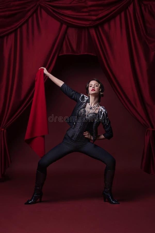 Foto da arte da jovem mulher da forma na fase com cortinas vermelhas foto de stock royalty free
