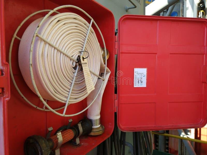 Foto da caixa do carretel da mangueira de fogo a bordo do equipamento de perfuração a pouca distância do mar imagem de stock