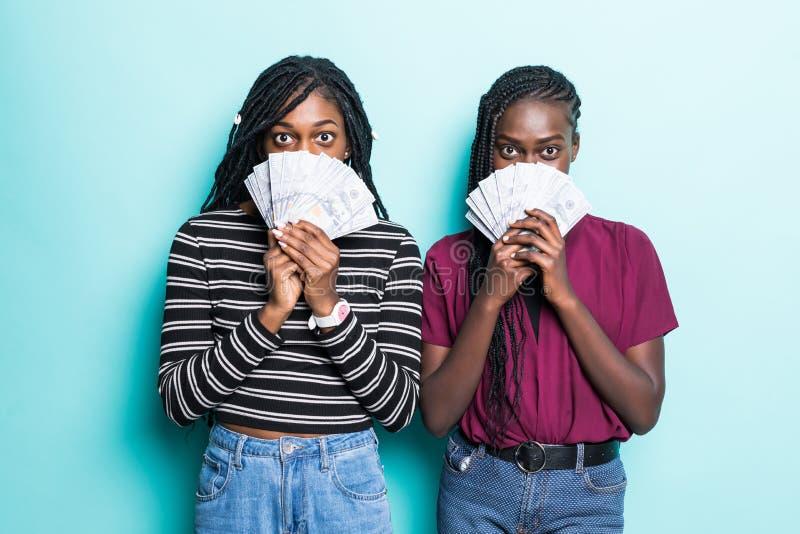 Foto da coberta das mulheres novas do afro-americano suas caras com as cédulas do dólar isoladas sobre o fundo azul imagens de stock