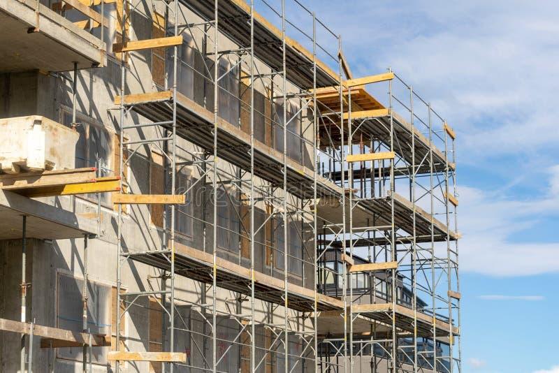 Foto da construção alta de vários andares da elevação com andaime foto de stock