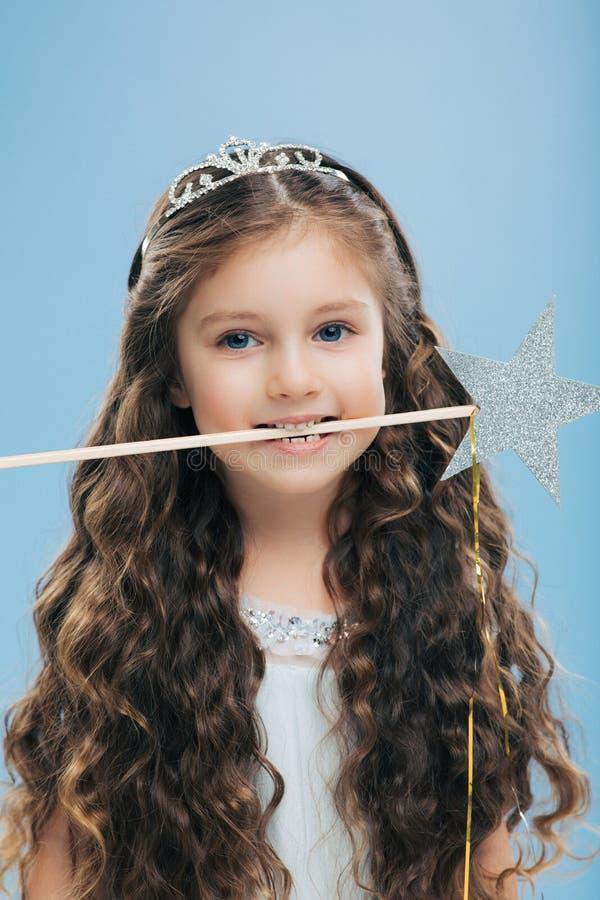 A foto da criança atrativa da mulher com aparência agradável, tem o cabelo escuro longo, guarda a varinha mágica na boca, poses s foto de stock
