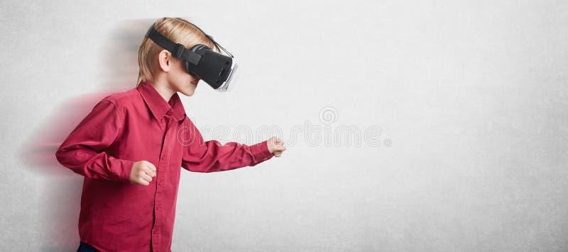 A foto da criança masculina usa auriculares da falha do oculus, olha alegre, gesticula ativamente, joga os jogos, poses contra o  fotografia de stock royalty free
