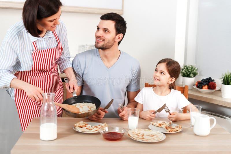 A foto da esposa de trabalho dura, o marido e sua filha sentam-se junto na mesa de cozinha, indo comer panquecas deliciosas foto de stock