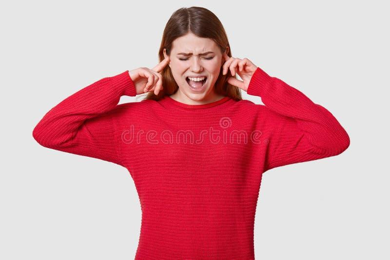 A foto da f?mea de cabelo escura fatigante, liga??o em ponte vermelha vestindo, estando no p?nico, n?o quer ouvir qualquer coisa, foto de stock royalty free