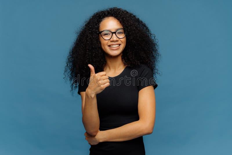 A foto da fêmea descascada escura bonita faz como o gesto, mantém o polegar acima, aprova algo bom, tem o sorriso agradável, vest foto de stock