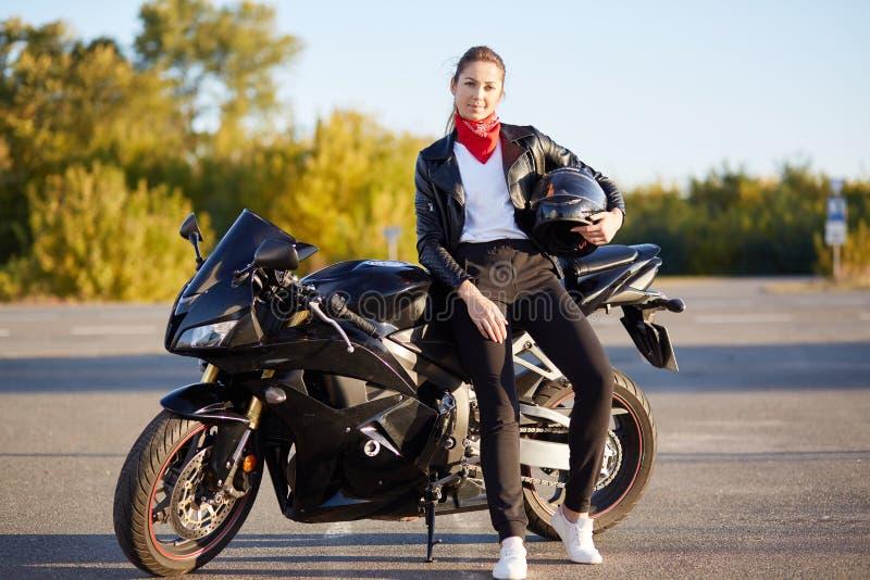 A foto da fêmea magro atrativa com ponitail, estando perto do motobike rápido preto com capacete à disposição, vestindo o equipam fotografia de stock