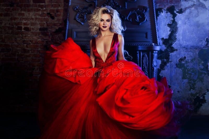 Foto da forma da mulher magnífica nova Corrida para a câmera Louro sedutor no vestido vermelho com saia macia imagens de stock royalty free