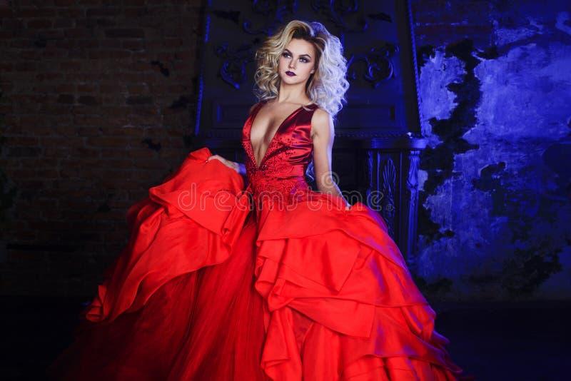 Foto da forma da mulher magnífica nova Corrida para a câmera Louro sedutor no vestido vermelho com saia macia imagem de stock