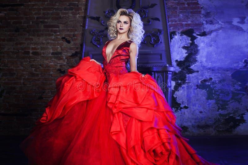 Foto da forma da mulher magnífica nova Corrida para a câmera Louro sedutor no vestido vermelho com saia macia fotos de stock royalty free