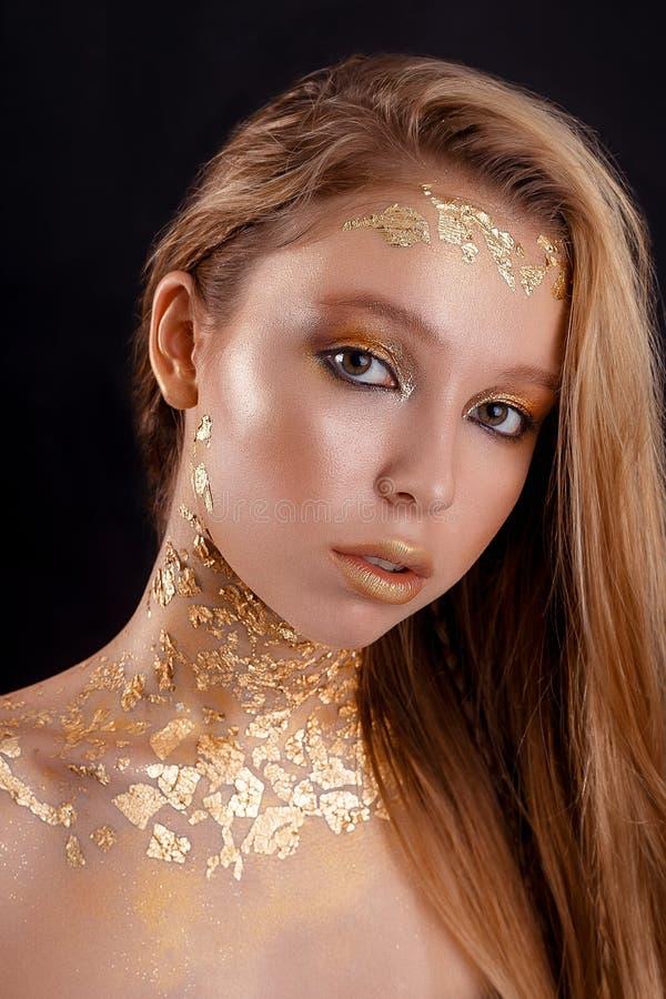 Foto da forma de uma mulher nova bonita feche acima da menina do retrato do ouro da beleza fotos de stock royalty free