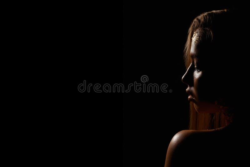 Foto da forma de uma mulher nova bonita Menina do retrato do ouro da beleza no fundo preto imagens de stock royalty free