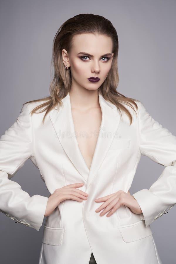 Foto da forma do estúdio da mulher elegante nova no revestimento do ` s dos homens brancos imagem de stock