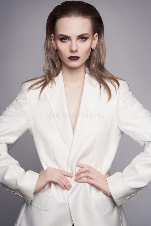 Foto da forma do estúdio da mulher elegante nova no revestimento do ` s dos homens brancos fotos de stock royalty free